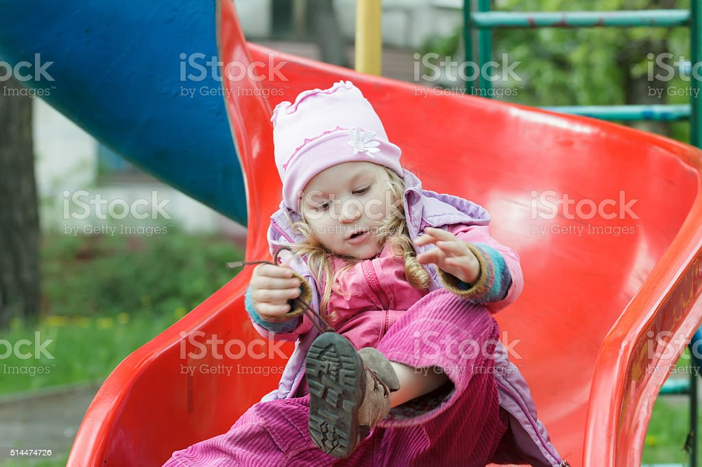 Little girl sitting on plastic playground slide and tying shoelaces stock photo