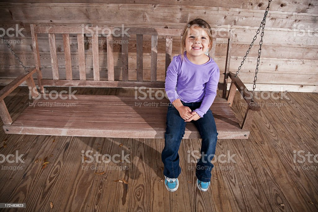 Little girl sitting on porch swing stock photo
