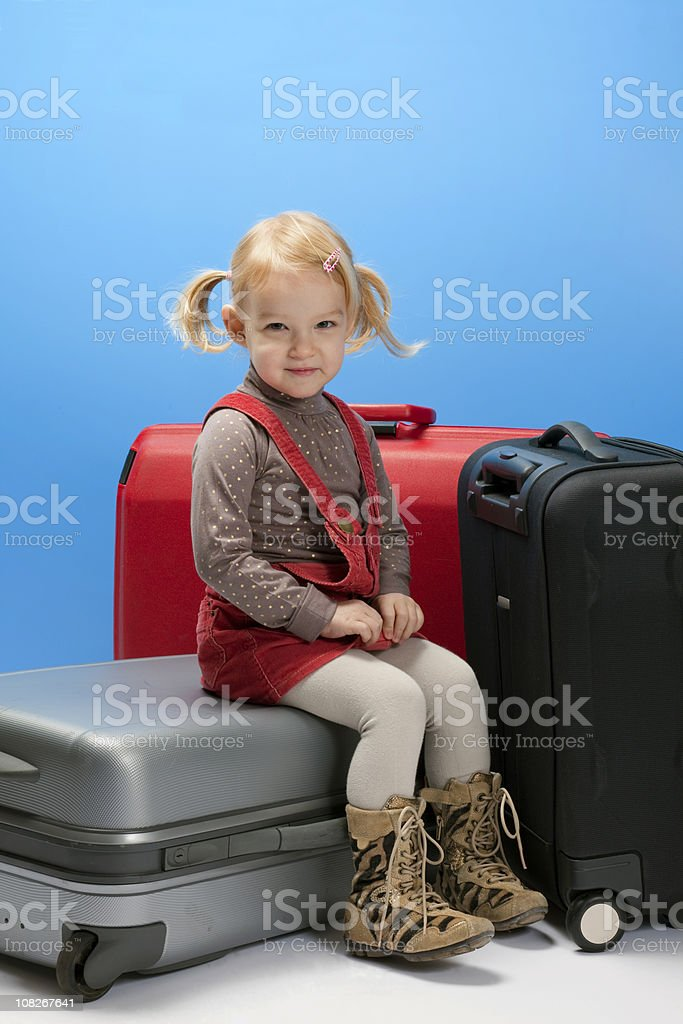 Little Girl Sitting on Rolling Luggage Suitcases royalty-free stock photo