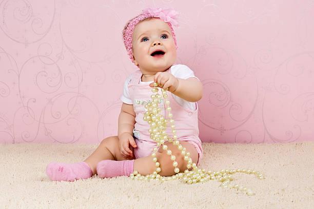 Niña sentada en el piso sosteniendo un collar de perlas - foto de stock