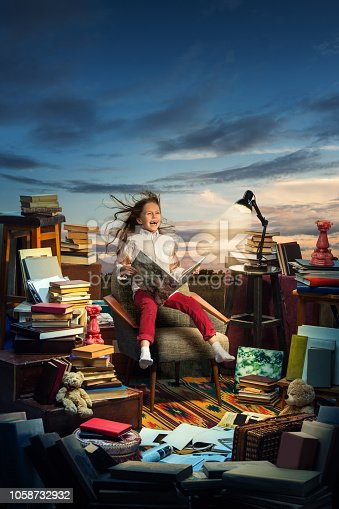 Little Girl sitting on the open books. Childhood dreams, creature and education concept.Wondering world. abstract collage