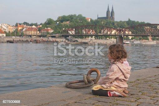 istock Little girl sitting thoughtfully on riverside 627500668