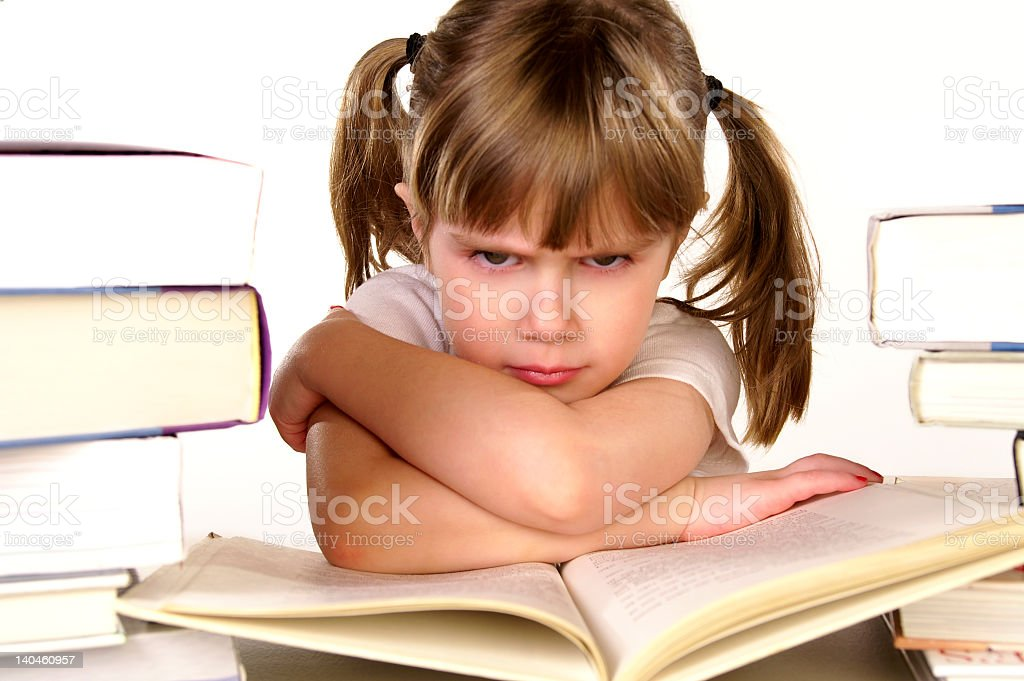 Little girl sitting with a grumpy expression on her face stock photo