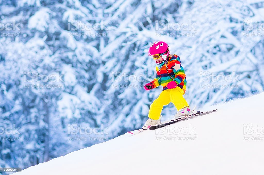 Little girl skiing in the mountains stock photo