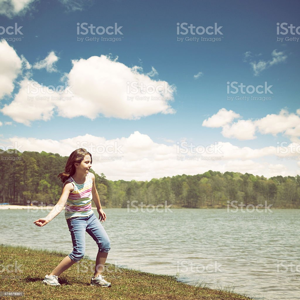 Little Girl Skipping Stones on a Lake stock photo