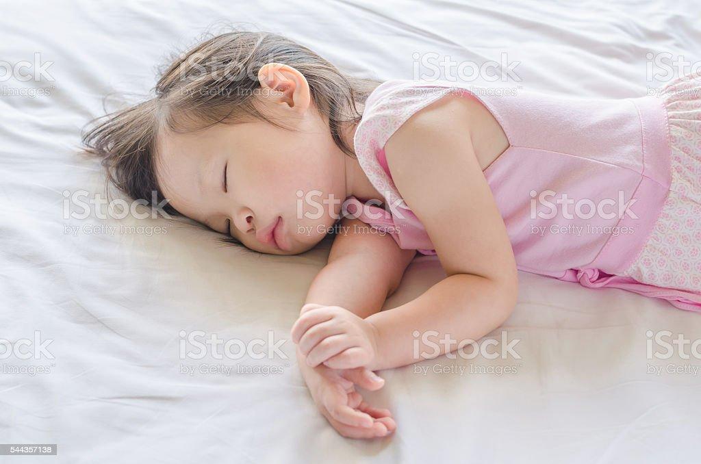 Little girl sleeping on bed stock photo