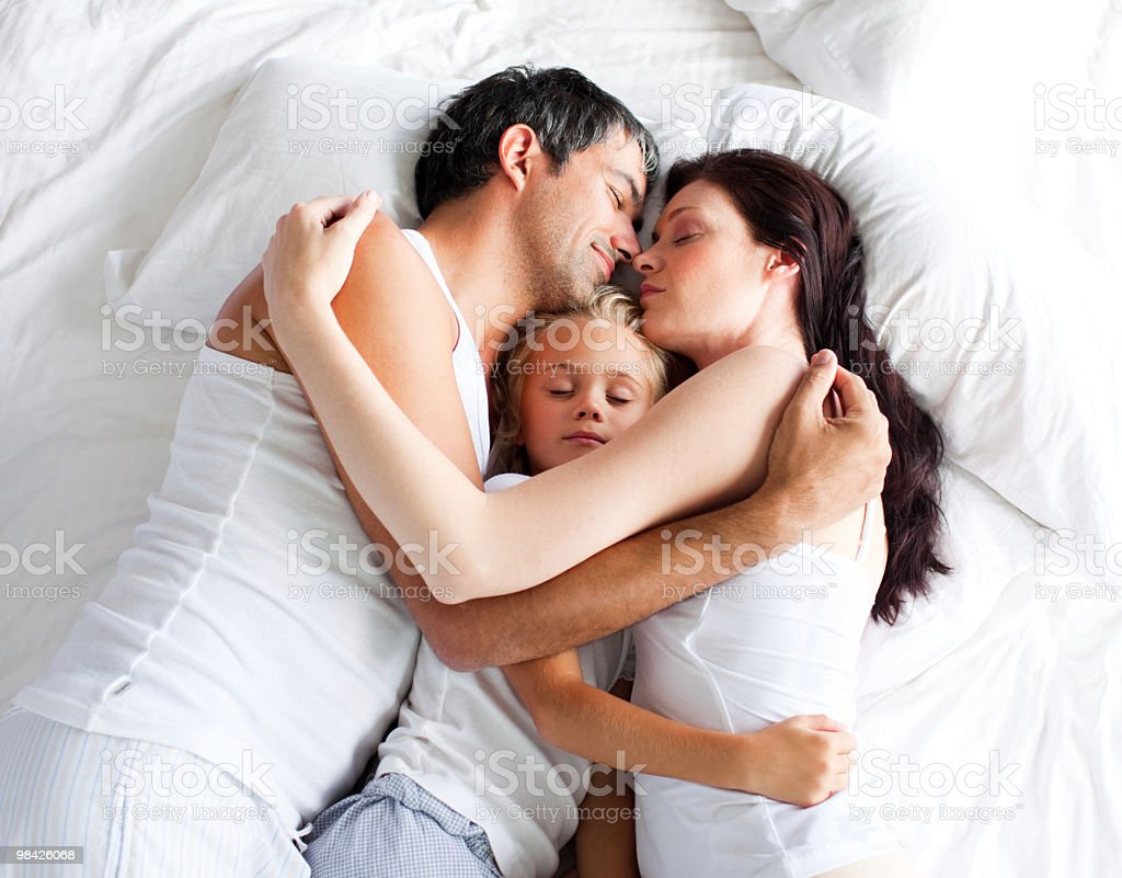 Little girl sleeping on bed with her parents royalty-free stock photo