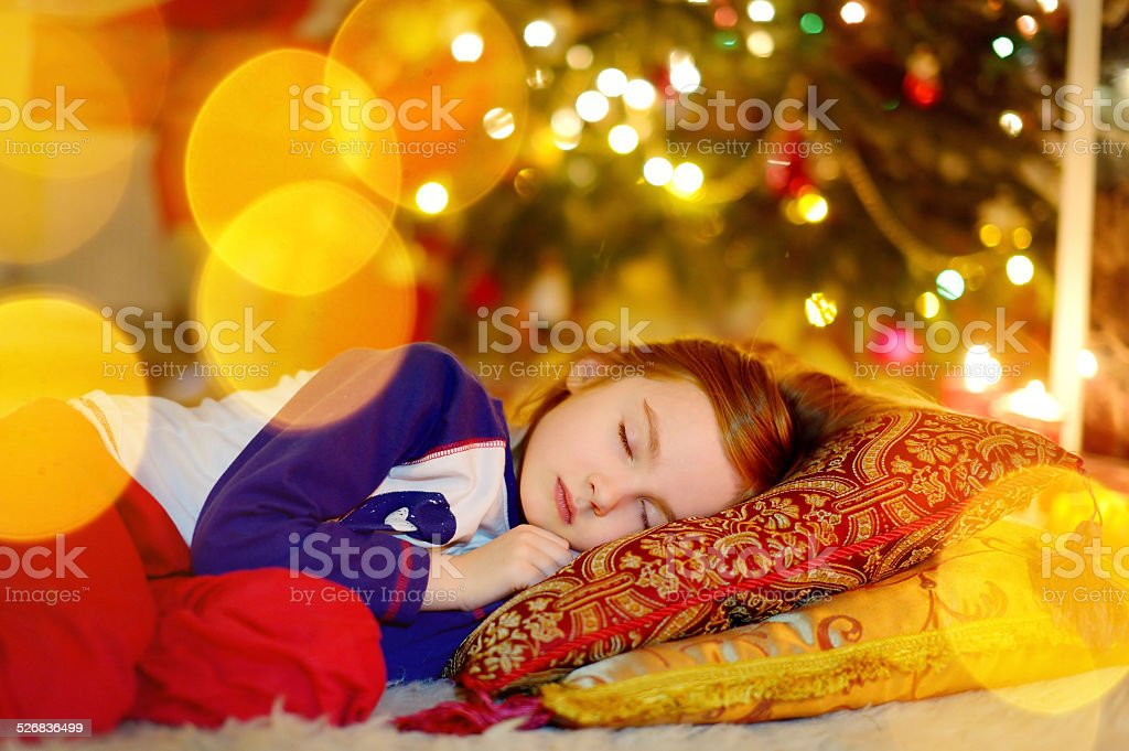 Little girl sleeping under the Christmas tree stock photo