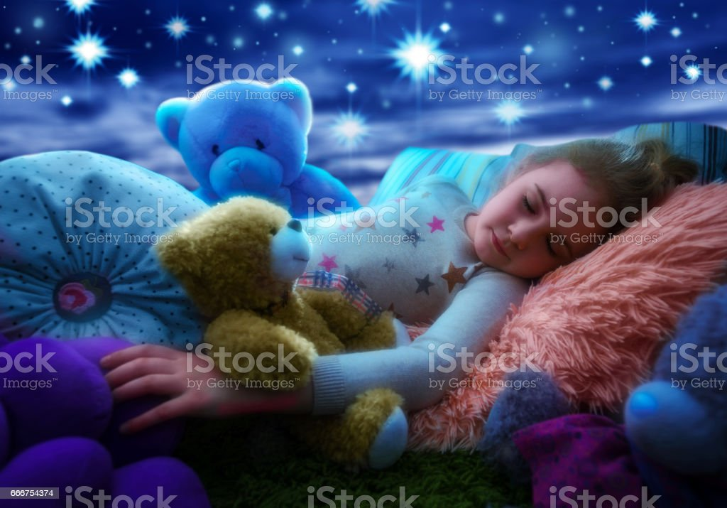 Little girl sleeping with teddy bear in bed, dreaming the starry sky at bedtime night stock photo