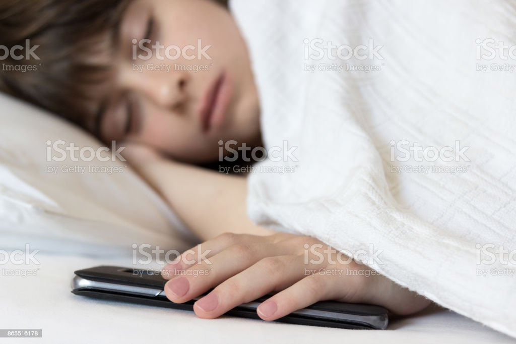 Little girl sleeps in the bed holding her cellphone. Problem of children's addiction to technologies and smartphones. stock photo