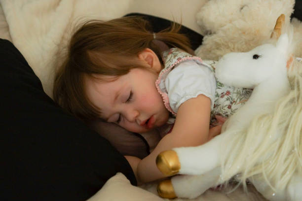 little girl sleeps with her cuddly - unicorn bed imagens e fotografias de stock