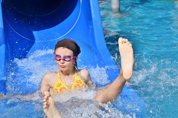 little girl sliding on the water slide during holiday stock photo