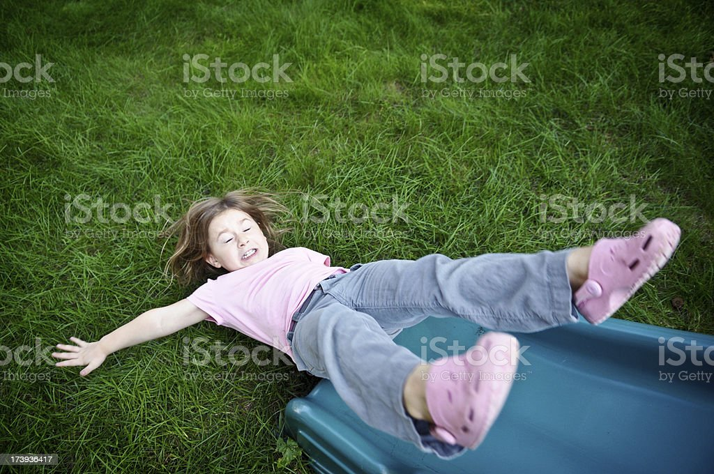 Little Girl Sliding Upside Down on a Slide stock photo