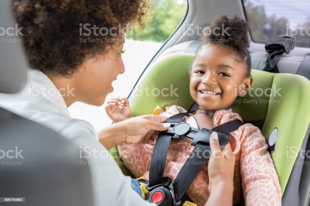 Little girl smiles as she is buckled into car seat stock photo