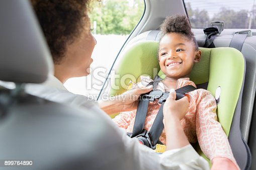 istock Little girl smiles at mother as she buckles her car seat harness 899764890