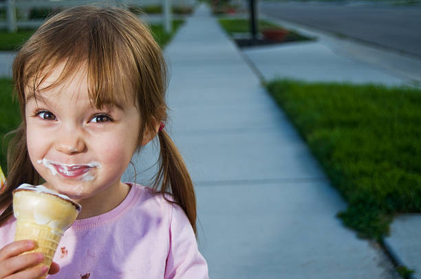 Little girl smiling and eating ice cream in summer stock photo