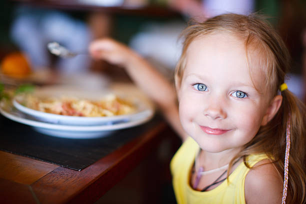 Little girl smiling and eating stock photo