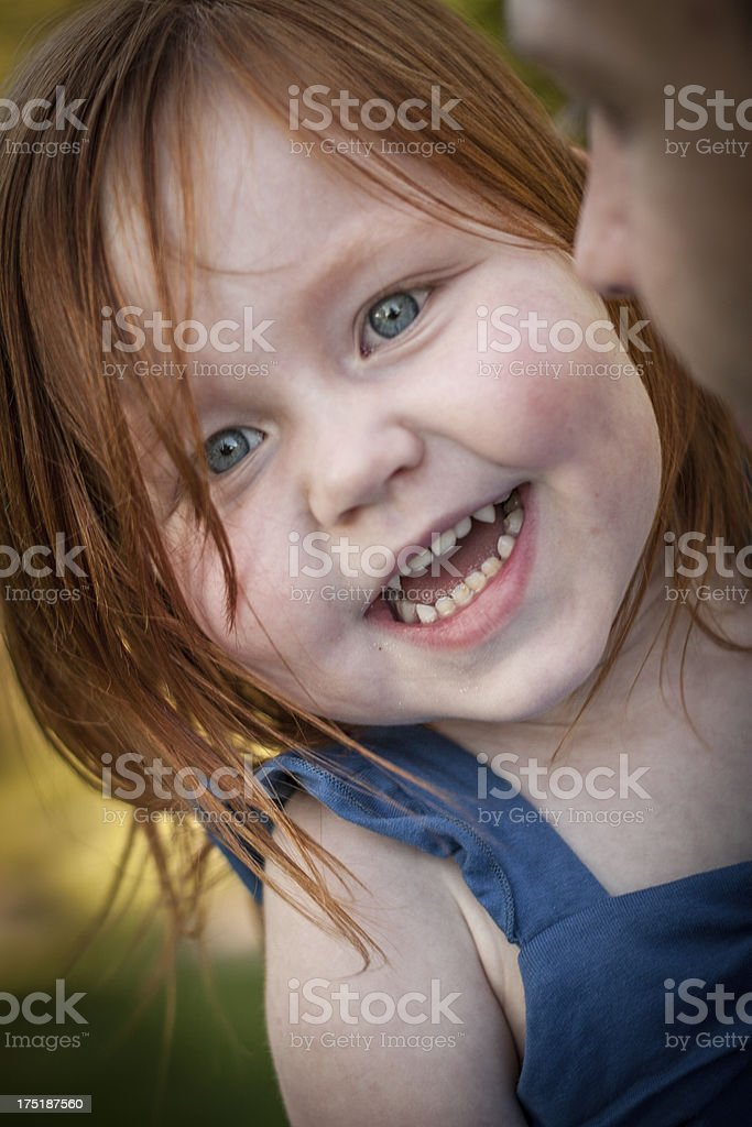 Little Girl Smiling While Dad Talks To Her Stock Photo