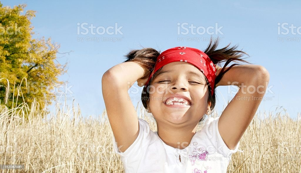 Little girl smiling with her hands in her hair over field stock photo