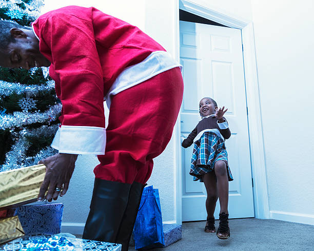 bambina dando dietro santa claus - santa claus tiptoeing foto e immagini stock