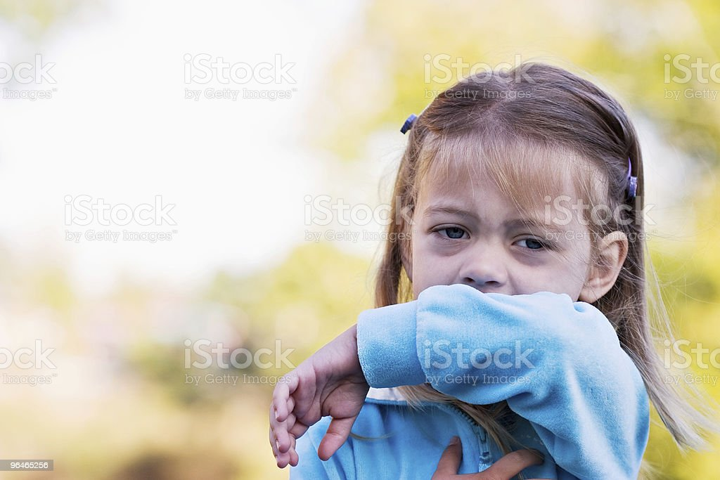 A little girl sneezing in to get elbow stock photo