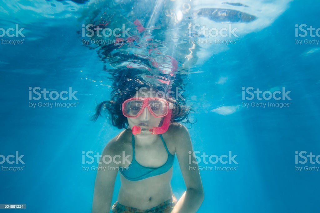 Little Girl Snorkeling Surrounded by Sunrays stock photo