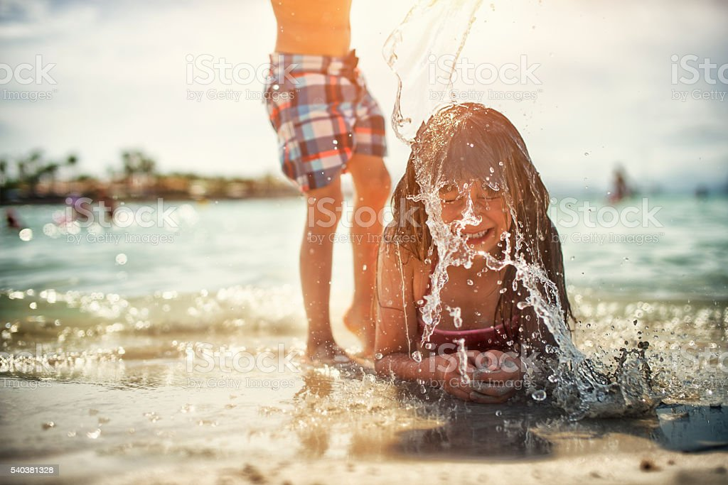 Little girl splashed with bucket of water stock photo