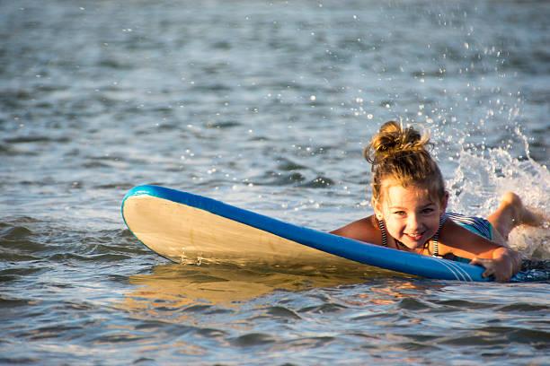 Little girl splashing around on surfboard stock photo