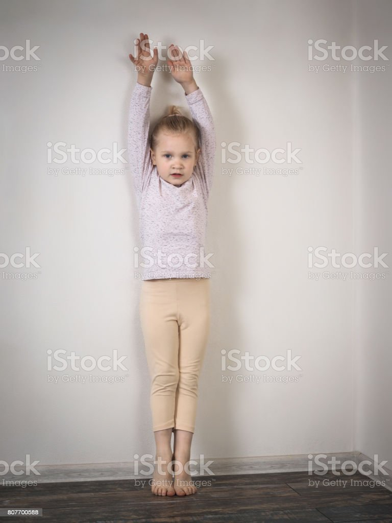 Little girl standing against the wall on tiptoe with raised arms. The child wants to grow up stock photo