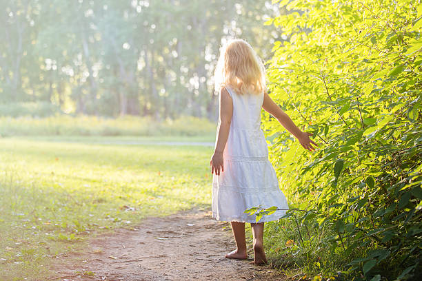 Little girl standing barefoot on a path stock photo