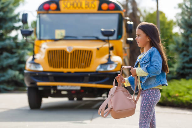 Little girl standing by a big school bus door with her pink backpack. stock photo