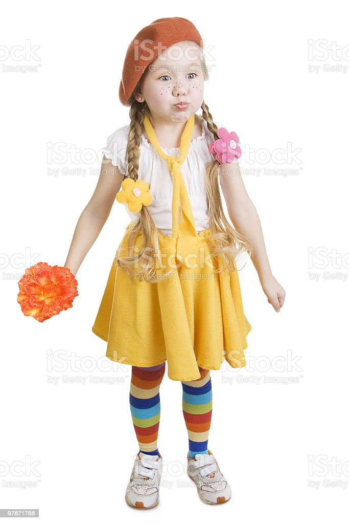 Little girl standing  holding a flower and grimacing. royalty-free stock photo