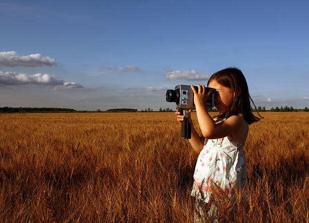Little Girl Standing in Field and Filming with Vintage Camera stock photo