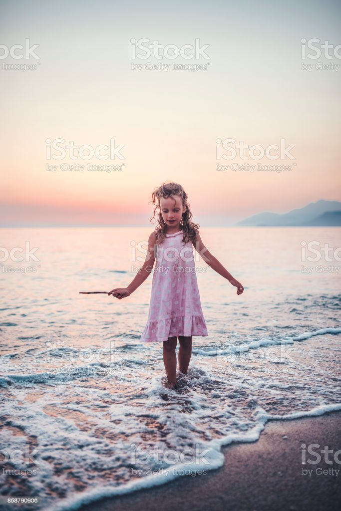 Little girl standing in the sea water stock photo