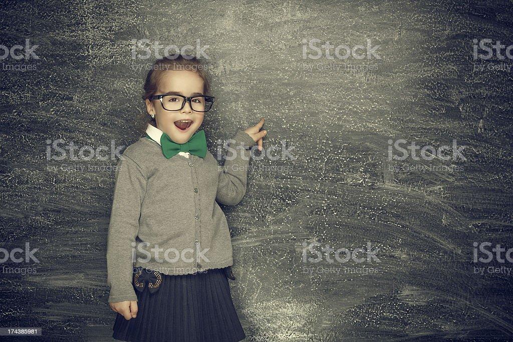 Little girl standing next to blackboard royalty-free stock photo