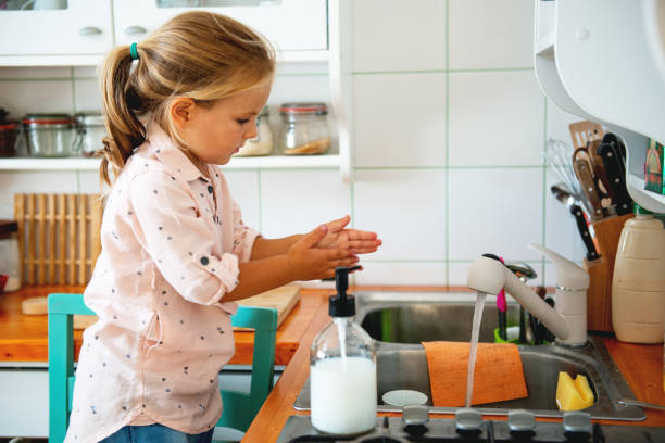 Little girl standing on a Chair, washing her hands stock photo