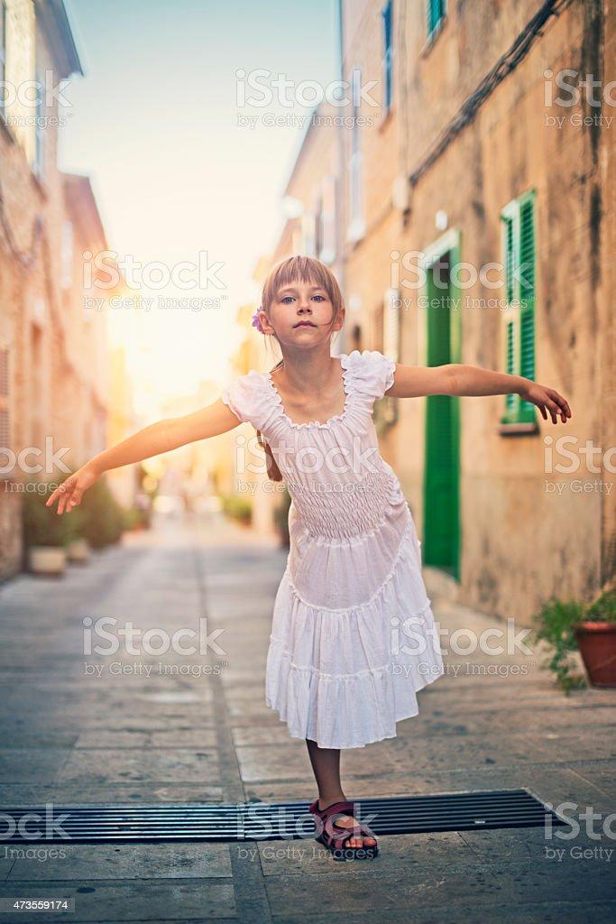 Little girl standing on one leg stock photo