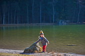 Little girl standing on the edge of water, touching stone and looking away