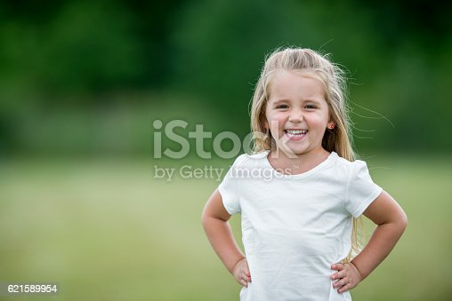 A cute preschool age girl is standing outside at the park and is smiling while looking at the camera.