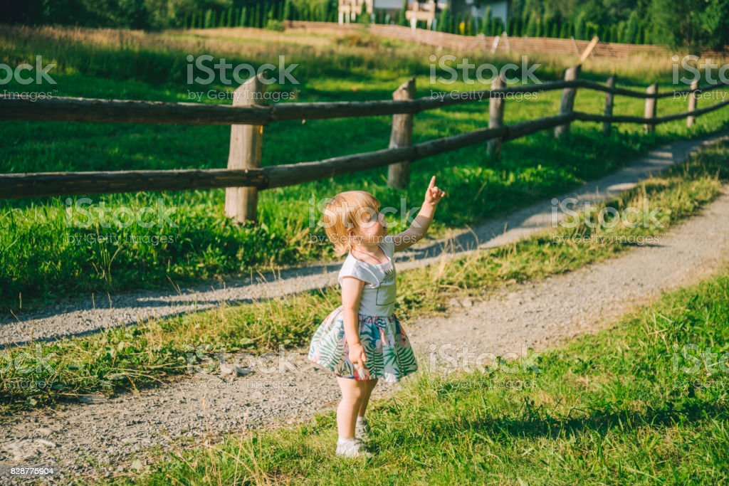 little girl stands on the country raod and point on somtheing stock photo