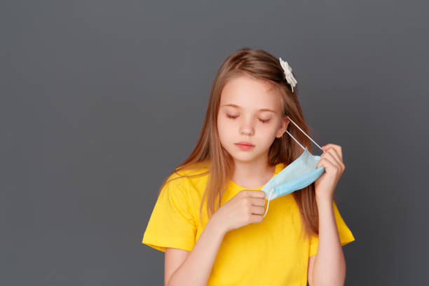 A little girl stands with a mask in her hand on a gray background, annoyed by the mask, she wants to take it off stock photo