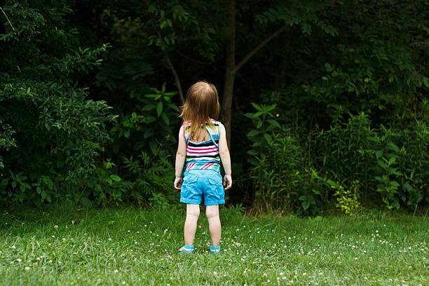 Little girl staring into woods stock photo