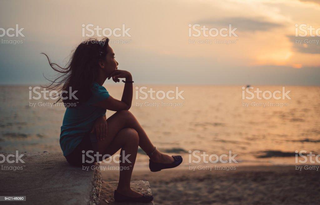 Little girl staring the sea stock photo