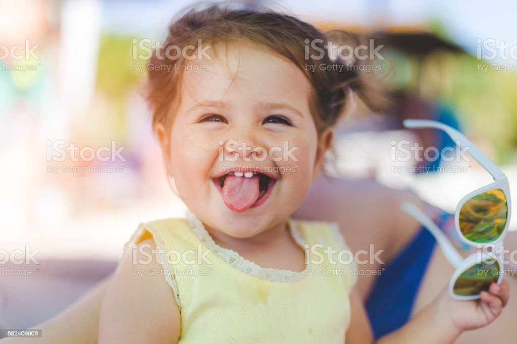 Little girl sticking her tongue out stock photo