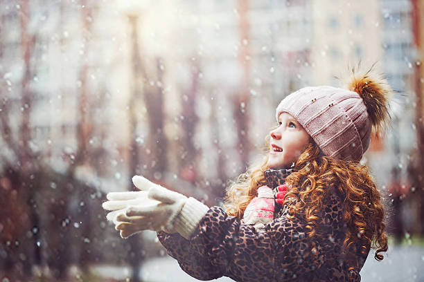 little girl stretches her hand to catch falling snowflakes. - flocon de neige neige photos et images de collection