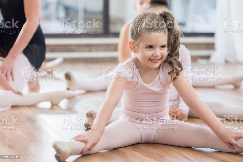 e54a581750c2 Little Girl Stretches Her Legs In Ballet Class Stock Photo   More ...