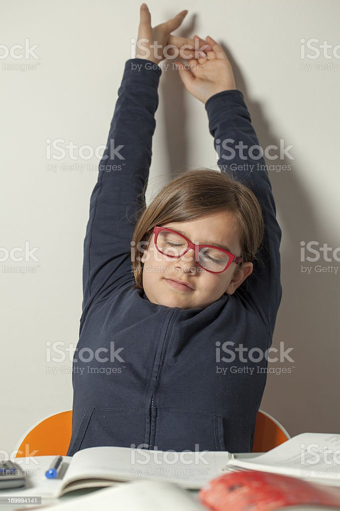 Little Girl Stretching After Finishing Her Homework stock photo