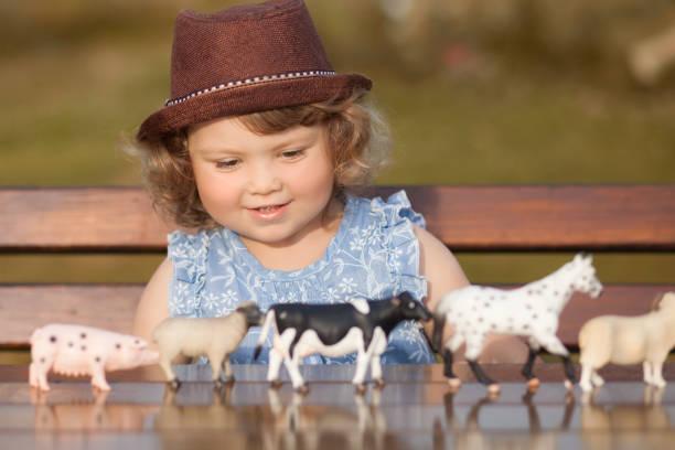 Little girl studying farm animals stock photo