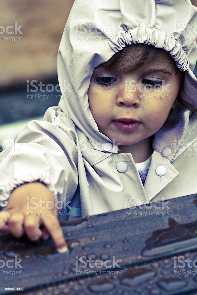 Little girl studying raindrops at the playground royalty-free stock photo