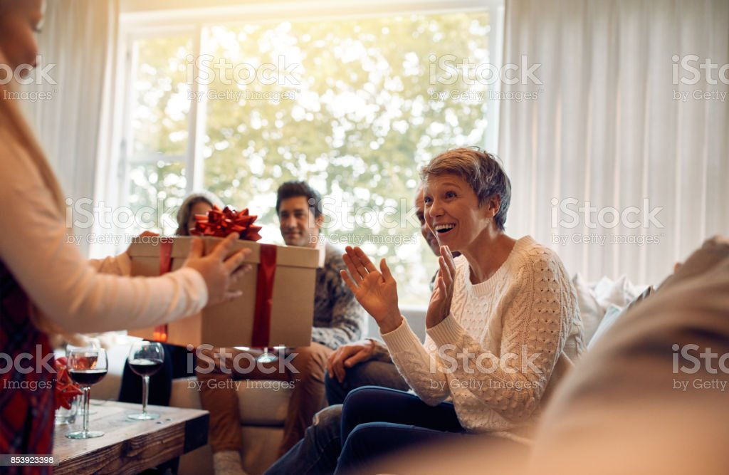 Little girl surprising her grandmother with a christmas present stock photo